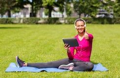 Mujer sonriente con PC de la tableta al aire libre Fotos de archivo libres de regalías