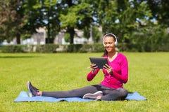 Mujer sonriente con PC de la tableta al aire libre Fotos de archivo