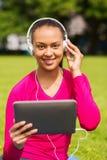 Mujer sonriente con PC de la tableta al aire libre Foto de archivo