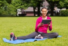 Mujer sonriente con PC de la tableta al aire libre Imagenes de archivo