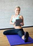 Mujer sonriente con PC de la tableta en gimnasio Imágenes de archivo libres de regalías