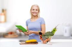 Mujer sonriente con PC de la tableta que cocina verduras Fotos de archivo