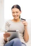 Mujer sonriente con PC de la tableta y la tarjeta de crédito Imagen de archivo libre de regalías