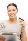 Mujer sonriente con PC de la tableta y la tarjeta de crédito Fotos de archivo libres de regalías