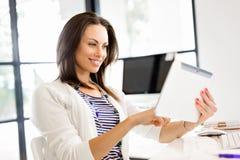 Mujer sonriente con PC de la tablilla Imágenes de archivo libres de regalías