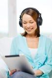 Mujer sonriente con PC y los auriculares de la tableta Fotografía de archivo