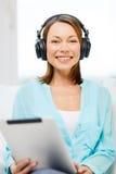 Mujer sonriente con PC y los auriculares de la tableta Fotos de archivo