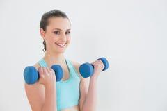 Mujer sonriente con pesas de gimnasia contra la pared Foto de archivo libre de regalías