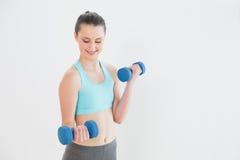 Mujer sonriente con pesas de gimnasia contra la pared Fotografía de archivo libre de regalías