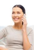 Mujer sonriente con smartphone en casa Foto de archivo libre de regalías