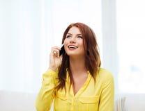 Mujer sonriente con smartphone en casa Fotografía de archivo libre de regalías
