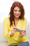 Mujer sonriente con smartphone en casa Imagen de archivo