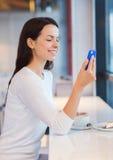 Mujer sonriente con smartphone y café en el café Imagen de archivo