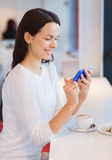 Mujer sonriente con smartphone y café en el café Foto de archivo