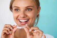 Mujer sonriente con sonrisa hermosa usando los dientes que blanquea la bandeja foto de archivo