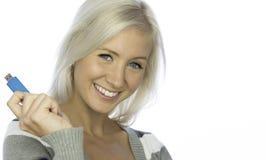 Mujer sonriente con sostener una pluma del usb Imagen de archivo libre de regalías