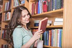 Mujer sonriente con un libro a disposición Foto de archivo libre de regalías