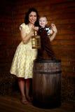Mujer sonriente con un niño que se coloca después Fotografía de archivo libre de regalías