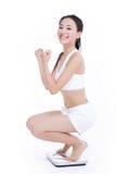 Mujer sonriente con una báscula de baño Imagen de archivo libre de regalías