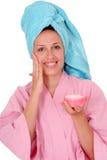 Mujer sonriente con una crema Imagenes de archivo