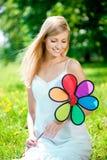 Mujer sonriente con una flor del arco iris al aire libre Imágenes de archivo libres de regalías