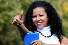 Mujer sonriente con una tableta que muestra el pulgar para arriba, al aire libre Imágenes de archivo libres de regalías
