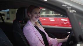Mujer sonriente confiada en la chaqueta rosada que se sienta en el coche, mirando en cierre del espejo retrovisor para arriba Muj metrajes