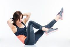 Mujer sonriente de la aptitud que hace ejercicios abdominales Imagen de archivo
