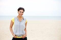 Mujer sonriente de la aptitud que se coloca en la playa Foto de archivo libre de regalías