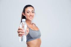 Mujer sonriente de la aptitud que sostiene la botella con agua Imagen de archivo