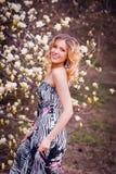 Mujer sonriente de la belleza cerca de la magnolia blanca Foto de archivo