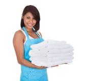Mujer sonriente de la criada con las toallas Fotos de archivo libres de regalías