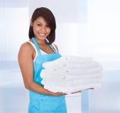 Mujer sonriente de la criada con las toallas Imágenes de archivo libres de regalías