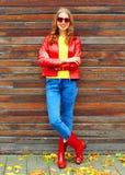 mujer sonriente de la moda del otoño que lleva una chaqueta de cuero roja Imagen de archivo libre de regalías