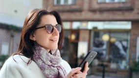 Mujer sonriente de la moda entusiasta de la calle que charla usando el smartphone al aire libre en el primer moderno de la ciudad almacen de metraje de vídeo