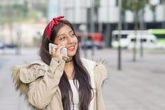Mujer sonriente de la moda que habla por el teléfono elegante en la calle Foto de archivo