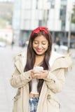 Mujer sonriente de la moda que usa el teléfono elegante Foto de archivo