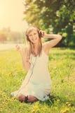 Mujer sonriente de la mujer que escucha la música en los auriculares al aire libre Imagenes de archivo