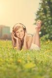 Mujer sonriente de la mujer que escucha la música en los auriculares al aire libre Fotografía de archivo libre de regalías
