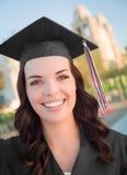 Mujer sonriente de la raza mixta de Graduatie en casquillo y vestido Foto de archivo libre de regalías