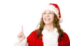 Mujer sonriente de Papá Noel que señala con el dedo para arriba Imagen de archivo libre de regalías