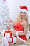 Mujer sonriente de santa cerca del árbol de navidad Foto de archivo libre de regalías