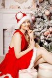 Mujer sonriente de santa de la belleza joven cerca del árbol de navidad Fashio Fotografía de archivo