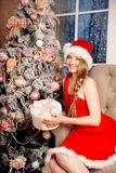 Mujer sonriente de santa de la belleza joven cerca del árbol de navidad Fashio Foto de archivo libre de regalías