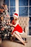 Mujer sonriente de santa de la belleza joven cerca del árbol de navidad Fashio Imágenes de archivo libres de regalías