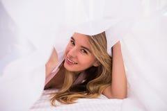 Mujer sonriente debajo de un edredón en su dormitorio Fotografía de archivo