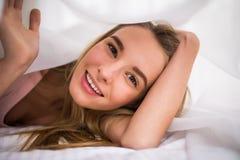 Mujer sonriente debajo de un edredón en su dormitorio Fotos de archivo libres de regalías