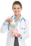 Mujer sonriente del doctor que pone el billete de banco de los euros en la hucha Fotografía de archivo libre de regalías
