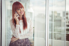 Mujer sonriente del inconformista que tiene una llamada de teléfono Foto de archivo libre de regalías