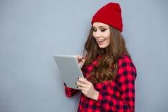 Mujer sonriente del inconformista que usa la tableta Imágenes de archivo libres de regalías